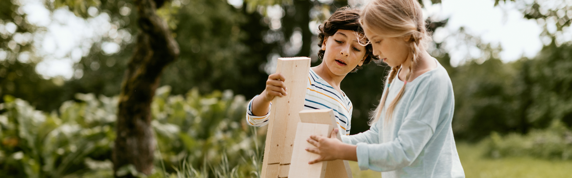Kids in the garden playing with wooden boards.